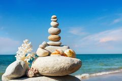 Rock zen of white stones, shells and coral on a background of the summer sea and blue sky. Concept of harmony and balance Stock Photos