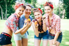 Group of friends at park having fun party. Cheerful girls with a cakes in hands. Retro style. stock photo