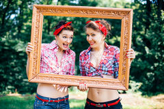 Rockabilly hen-party in park.  Smiling girls holding frame Stock Photo