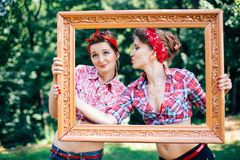 Rockabilly hen-party in park. Smiling girls holding frame Royalty Free Stock Photography