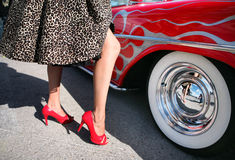 Rockabilly and Red Muscle car. A woman dressed as Rockabilly, the hip culture of the 1950s style, stands next to a red muscle car with whitewalls Royalty Free Stock Photos