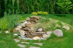 Rockary in de vorm van een bergwaterval in de tuin met stenen en vele verschillende bloemen en installaties royalty-vrije stock foto's
