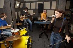 Rockband im Studio. Sängermädchen singt Lizenzfreies Stockbild