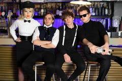 Rockbandet för fyra barn i svartvitt poserar Arkivbild