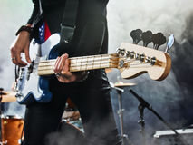 Rockbandet utför på etapp Basist i förgrunden Arkivfoto