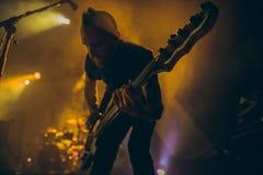 Rockbandet utför på etapp Gitarristen spelar solo Kontur av gitarrspelaren i handling på etapp framme av konsertfolkmassan Arkivbilder