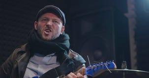 Rockbandvokalist som sjunger och spelar gitarren på repetitionen arkivfilmer