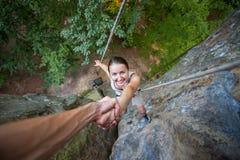 Rockclimber помогая к женскому альпинисту достигнуть верхнюю часть горы Стоковые Фотографии RF