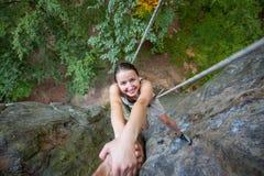 Rockclimber aidant au grimpeur féminin à atteindre le dessus de la montagne Images libres de droits