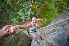 Rockclimber, das zum weiblichen Bergsteiger hilft, Spitze des Berges zu erreichen Lizenzfreie Stockbilder