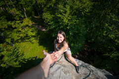 Rockclimber helping to female climber to reach top of mountain Stock Photography