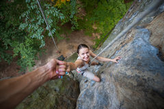 Rockclimber helping to female climber to reach top of mountain. A strong man rock climber is helping a sporty female climber by hand on a rocky wall. View from Stock Images