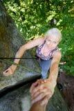 Rockclimber pomaga żeński arywista dosięgać wierzchołek góra Zdjęcia Stock