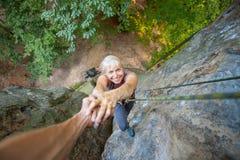 Rockclimber pomaga żeński arywista dosięgać wierzchołek góra Obrazy Royalty Free