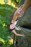 Rockclimber que ajuda ao montanhista fêmea a alcançar a parte superior da montanha Imagem de Stock Royalty Free
