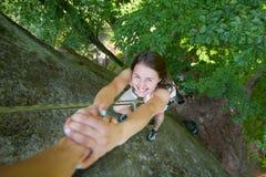 Rockclimber que ajuda ao montanhista fêmea a alcançar a parte superior da montanha Fotos de Stock Royalty Free
