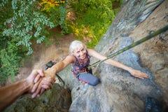 Rockclimber que ayuda al escalador femenino a alcanzar el top de la montaña Fotografía de archivo