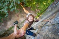 Rockclimber que ayuda al escalador femenino a alcanzar el top de la montaña Foto de archivo