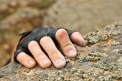 Rockclimber's hand on granite rock in gloves Royalty Free Stock Photos