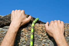 Rockclimber's hands and rope Stock Photo