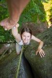 Rockclimber som hjälper till den kvinnliga klättraren att nå överkanten av berget arkivbilder