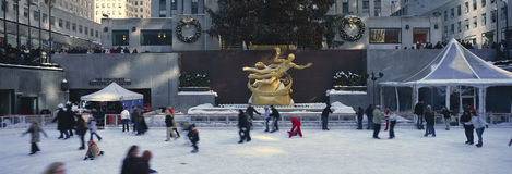 Rockefeller Square and ice skating rink and ice skaters at Christmas time with snow in mid-town Manhattan, NY Royalty Free Stock Photography