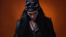 Rocker που ισιώνει τη μακριά μαύρη τρίχα του, που φορά το σακάκι δέρματος και το bandana, προσβολή σε αργή κίνηση απόθεμα βίντεο