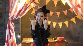 Rocker το κορίτσι παρουσιάζει κέρατα με τα δάχτυλά του φιλμ μικρού μήκους