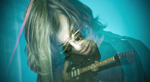 Rocker. Playing electric guitar over blue background, zoom and strobe lighting royalty free stock photos