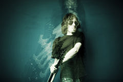 Rocker in action. Rocker smashing electric guitar over blue background, zoom and strobe lighting royalty free stock photo