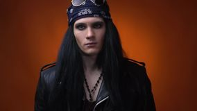 Rocker with bandana, leather jacket and beads, lifting his head, slow motion. A guy wearing leather jacket, bandana with glasses, and beads, lifting his head stock video footage