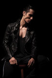 Rocker in black leather jacket posing seated in dark studio Stock Photography