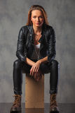Rocker in black leather jacket posing seated in studio while res Royalty Free Stock Photos