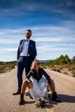 Rocker bride with black leather jacket, boots and sunglasses sitting on a suitcase in the middle of a lonely road and her groom po. Ses behind her in a rural stock photography
