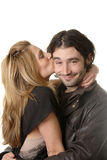Rocker Couple in Love. A young rock n roll couple, with girl kissing smirking boy on cheek Stock Photography
