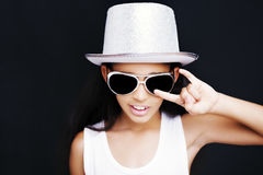 Rocker des kleinen Mädchens mit Sonnenbrille und Hut auf einem schwarzen Hintergrund Stockfoto