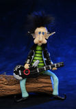 Rocker dwarf playing the guitar. Sat on a trunk. Blue background Stock Images