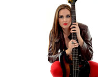Rocker girl. Young woman with leather jacket and red pants holding an electric bass guitar Stock Image