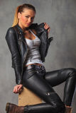 Rocker girl in leather posing seated on box while fixing her jac Stock Photography