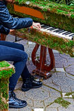 Rocker girl singing at one piano decorated with flowers Stock Images