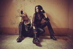 Rocker girls. Two rocker girls with cigarette and bottle of alcohol sitting on the floor royalty free stock images