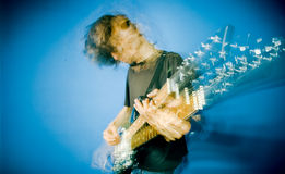 Rocker and guitar. Young man playing electric guitar over blue background, zoom and strobe lighting Stock Photos