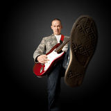 Rocker with guitar and foot. Rocker with electric guitar putting foot in camera Stock Image