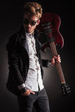 Rocker holding his guitar on shoulder and looking back Royalty Free Stock Photos