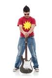 Rocker holds guitar between legs Stock Image