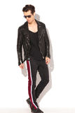 Rocker man in leather jacket and sunglasses walking Stock Image