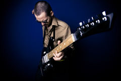 Rocker playing guitar. Alternative rocker playing intensely on his guitar. Dark blue background and vignette Royalty Free Stock Image