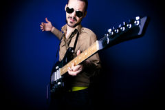 Rocker playing guitar. Alternative rocker playing intensely on his guitar. Dark blue background and vignette Stock Image