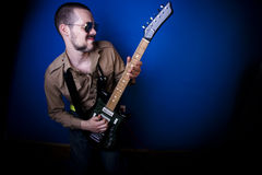 Rocker playing guitar. Alternative rocker playing intensely on his guitar. Dark blue background and vignette Royalty Free Stock Photos