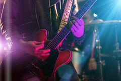 A rocker is playing guitar on stage. Royalty Free Stock Photos